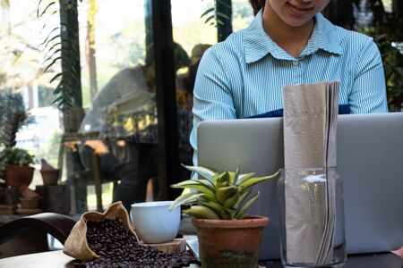 A woman using laptop to work and drink coffee in a coffee shop.