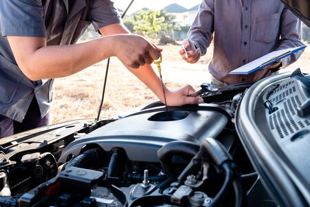 Repairman and insurance agent Checking engine order using modern tools.