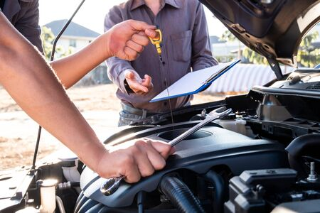 Repairman and insurance agent Checking engine order using modern tools. Stockfoto
