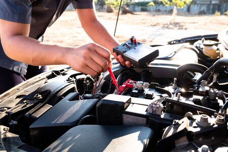 The hands of the repairman are checking the order of the engine using modern tools. Stockfoto