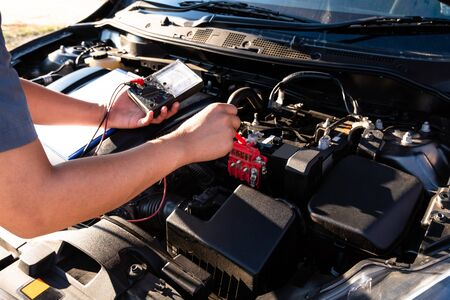 The hands of the repairman are checking the order of the engine using modern tools.
