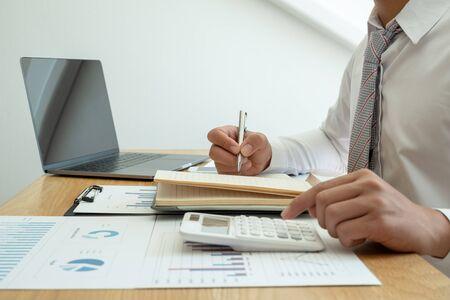 Ein Geschäftsmann sitzt an einem Schreibtisch und berechnet Finanzdiagramme zu den Ausgaben für Immobilieninvestitionen.