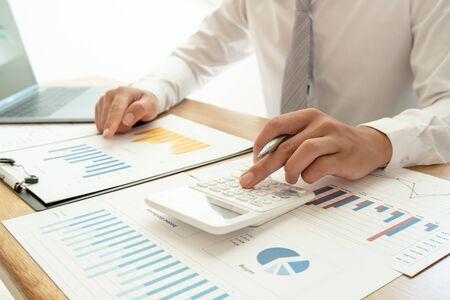 Un hombre de negocios está sentado en un escritorio y calcula gráficos financieros sobre gastos de inversión inmobiliaria.