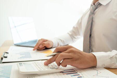 Un uomo d'affari è seduto a una scrivania e calcola grafici finanziari sulle spese per investimenti immobiliari.