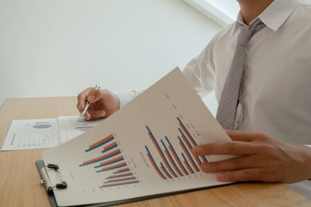 A business man is sitting at a desk and calculating financial graphs about real estate investment expenditures.