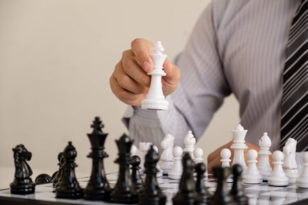 hand of businessman moving chess in competition, shows leadership, followers and business success strategies. Banque d'images - 140088594