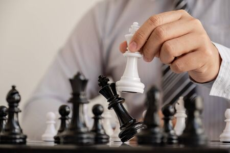 hand of businessman moving chess in competition, shows leadership, followers and business success strategies. Banque d'images - 140088524