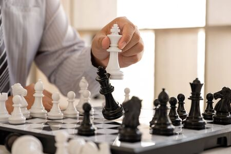 hand of businessman moving chess in competition, shows leadership, followers and business success strategies. Banque d'images - 140088560