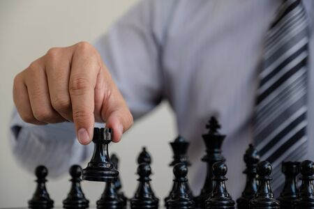 hand of businessman moving chess in competition, shows leadership, followers and business success strategies. Banque d'images - 140088528