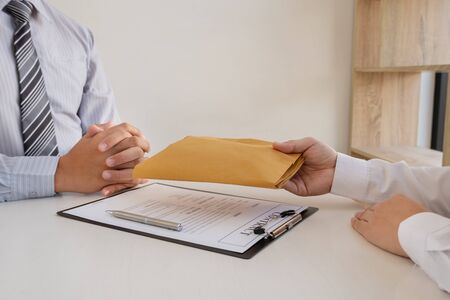 Businessmen make an agreement with money in an envelope proposed to a partner to bribe in the company. The concept of corruption. 스톡 콘텐츠