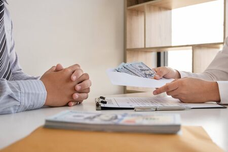 Businessmen make an agreement with the money proposed his partner to bribe in the company. The concept of corruption. 스톡 콘텐츠