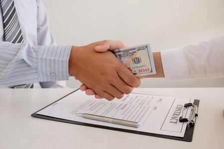 photo of Businessmen shake hands and dollar note, sign a contract to bribe corruption in the company. The concept of bribery and corruption. 스톡 콘텐츠