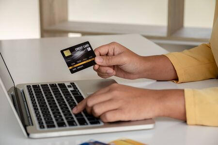 Young lady use credit cards and laptops for online shopping and making payments the internet.