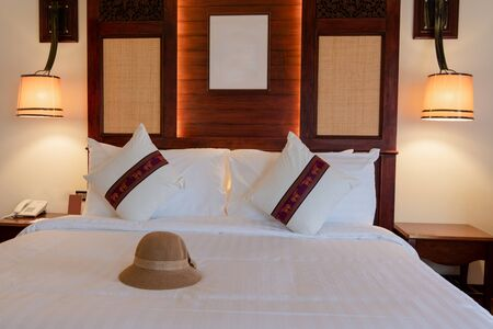 Photos of hats placed in the bed of a comfortable room in the hotel. Stock fotó