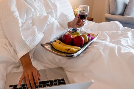 The hand of Young woman that hold wine glass And Sit play laptop In a luxurious room Ready Fruit.