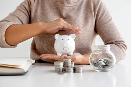 Women are putting coins in a piggy bank, glass bottle, saving money with coins, stepping into a growing business to succeed and save for retirement ideas.