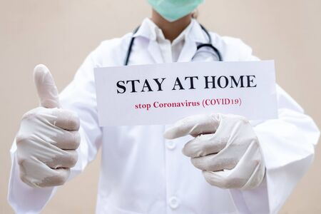 A female doctor who has paper in the hands of STAY AT HOME to prevent infection the spread of the covid virus. -19 medical concepts and health care.