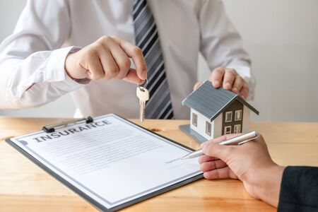 Real estate agent broker hand over the house key to the new owner after completing the signing according to agreement renting a house and buy house insurance Home insurance concept. 免版税图像