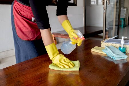 The happy housewives in rubber gloves wipe the dust with a spray while cleaning the tables and chairs cleaning concept.