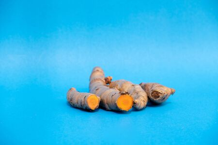 turmeric fresh on blue background. concept healthy spice diet.