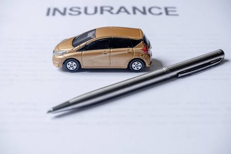 Car and pen on insurance documents. Car insurance concept.