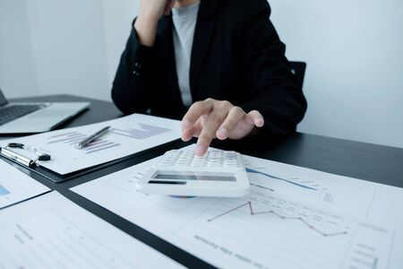 business female is sitting at a desk and use calculator calculating financial graph that show results In the office.
