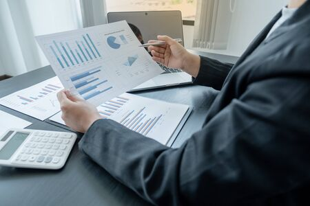 business female is sitting at a desk and calculating financial graph that show results.