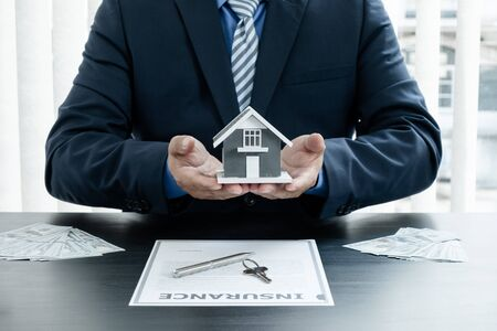 The hand of the real estate agent has a sample house with home insurance documents and keys to present to his clients who have made a purchase. Home insurance sales concept.