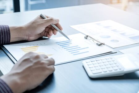 The hands of a male businessman are analyzing and calculating the annual income and expenses in a financial graph that shows results To summarize balances overall in office.