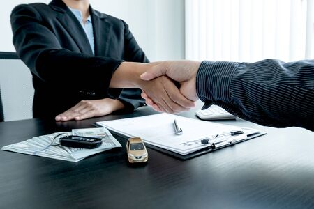 shaking hands, Car dealership provides advice about insurance details and car rental information and delivers the keys after signing the rental contract. Stockfoto