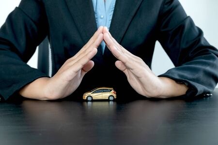 The car is covered by a woman's hand protecting the client the buyer of the car. Rental and insurance concepts. Stockfoto