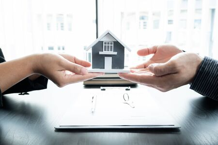 The real estate agent gives the house to a new owner's client after completing the signing of the lease and formally completing home insurance. Rental and insurance concepts.