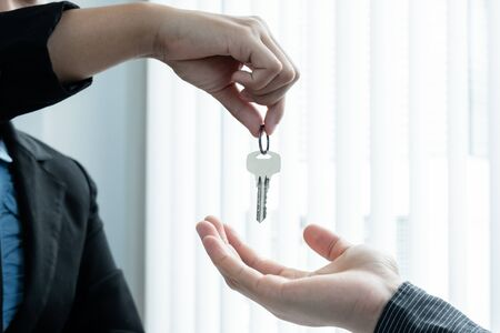 Real estate agent broker hand over the house key to the new owner after completing the signing according to agreement renting a house and buy house insurance officially completed. 스톡 콘텐츠