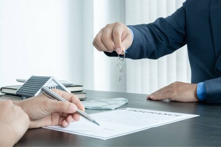 Real estate agent broker hand over the house key to the new owner after completing the signing according to agreement renting a house and buy house insurance officially completed. 免版税图像