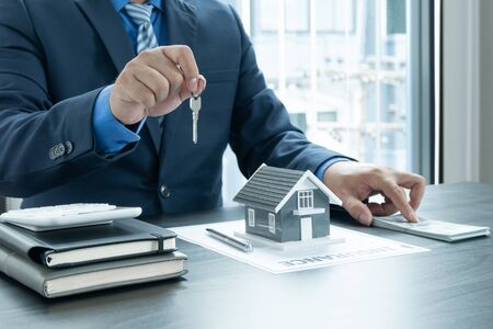 The hands of the real estate agent are holding the keys along with the house insurance contract documents and samples of the house designs to present to his clients at the appointment.