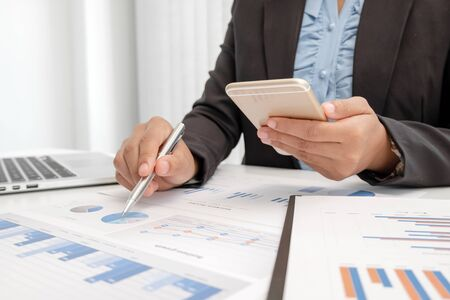 The hands of a male businesswoman are analyzing and calculating the annual income and expenses in a financial graph that shows results To summarize balances overall in office.