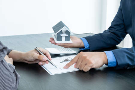 A real estate agent with a home model is talking to clients about renting a house and buying home insurance and contracting the contract after the formal negotiation is completed. Foto de archivo