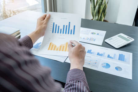 The hands of a male businessman are analyzing and calculating the annual income and expenses in a financial graph that shows results To summarize balances overall in office. Stock fotó
