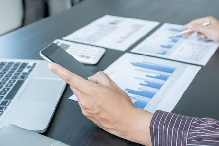 The hands of a male businessman are analyzing and calculating the annual income and expenses in a financial graph that shows results To summarize balances overall in office. Imagens