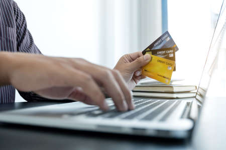 The businessman's hand is holding a credit card and using a laptop for online shopping and internet payment in the office. Stok Fotoğraf