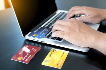 The businessman's hand is holding a credit card and using a laptop for online shopping and internet payment in the office.