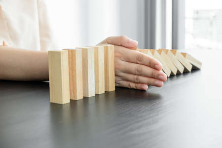 Hands of businesswoman stop block a wood game, gambling placing a wooden block. Concept Risk of management and strategy plan, protect business to success.