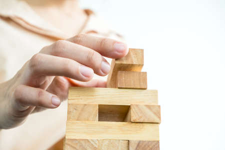 Hands of businesswomen playing wooden block game. Concept Risk of management and strategy plans for business growth and success. 스톡 콘텐츠 - 150939231