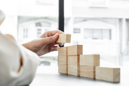 Hands of businesswomen playing wooden block game. Concept Risk of management and strategy plans for business growth and success.