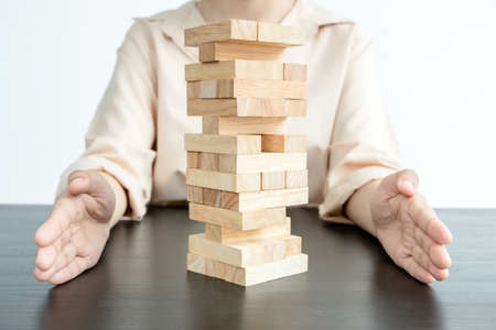 Hands of businesswoman prevent wooden blocks, gambling placing wooden blocks. Concept risk of management and strategy plans for business growth and success. 스톡 콘텐츠