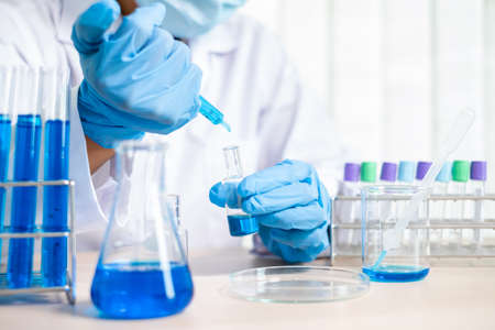 Medical scientists released a sample pipetted into a test flask to analyze the virus in a chemical laboratory. Scientific research concepts.