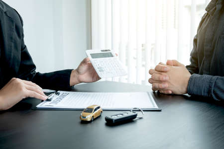 The car dealer advises the customer about insurance details and car rental information Ready delivers the keys after signing the rental contract.