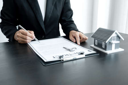 The hand of the real estate agent, holding a pen and drafting an agreement on the home insurance contract documents, along with samples of house models and keys to present to his clients.