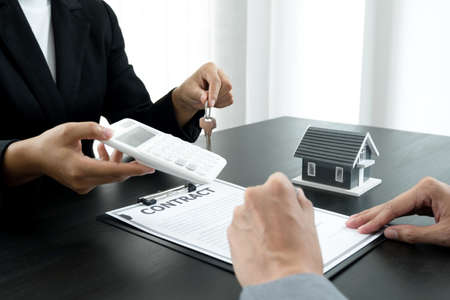 Real estate agent broker hand over the house key to the new owner after completing the signing according to agreement renting a house and buy house insurance Home insurance concept. Stock fotó