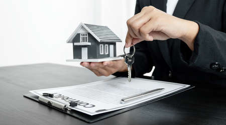The hands of the real estate agent are holding the keys along with the house insurance contract documents and samples of the house designs to present to his clients at the appointment. Stock fotó